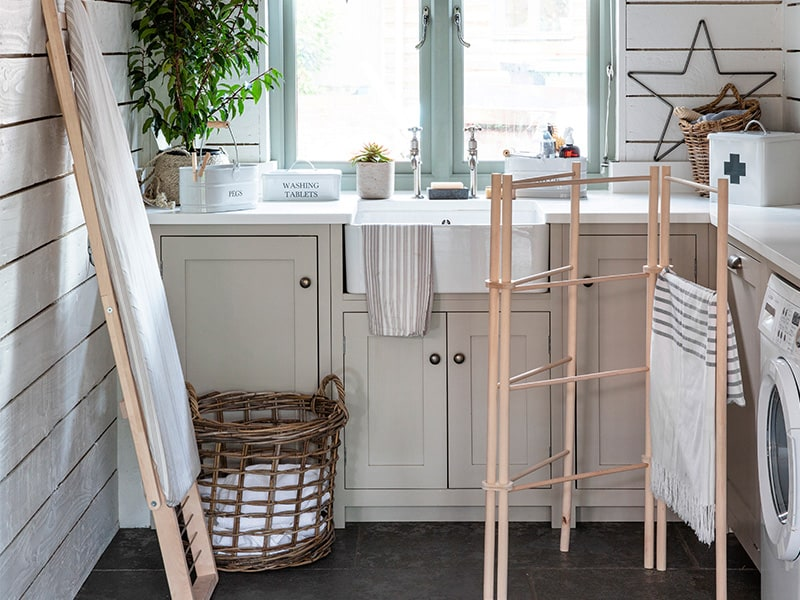 Utillity room with laundry items including ironing board, wooden dryer and laundry basket